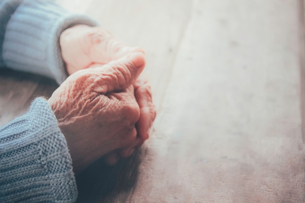The old person's praying hand. concept: hope, belief, dramatic loneliness, sadness, depression, disappointed, healthcare, pain.