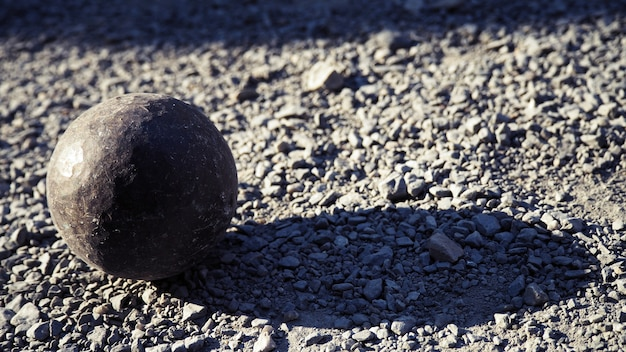 Old petanque balls on the ground. steel ball on the ground. light and shadow.