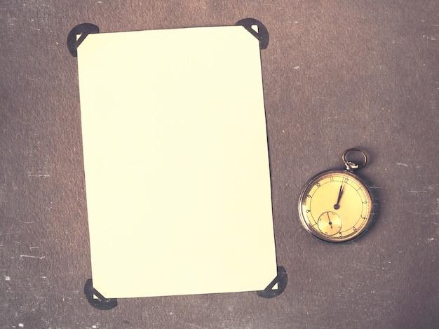 Страница старого фотоальбома с фотографиями и карманными часами