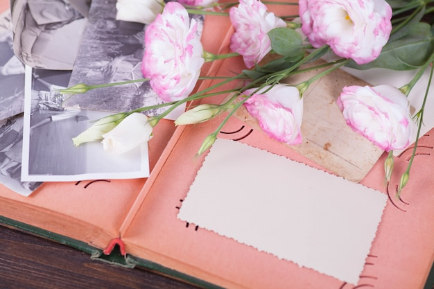 Old photo album, photos, camera, tender pink flowers on a dark wooden background.