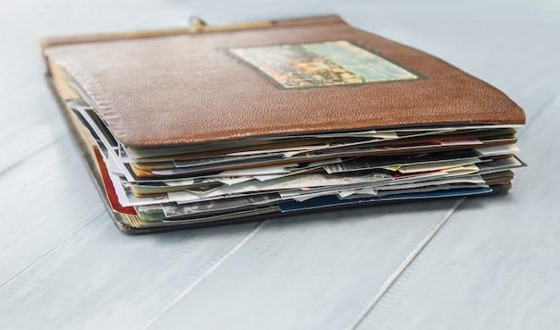 Старый фотоальбом с фотографиями на деревянном столе.