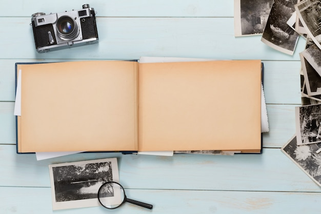 Old photo album with photos on a wooden table and an old camera.
