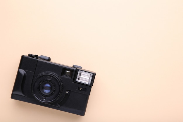 Old photo camera on beige background