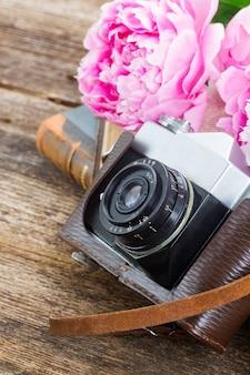 本とピンクの牡丹の花と古い写真カメラ