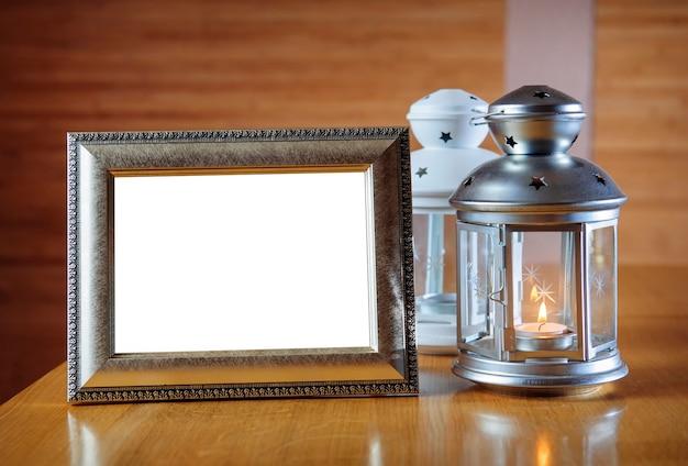 Старая фоторамка на деревянном столе и фонарь со свечой.