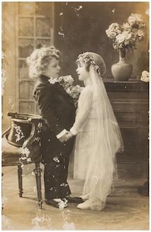 ウェディングドレスのドレスを着たかわいい子供たちの古い写真。実例となる画像、人間の関心の対象