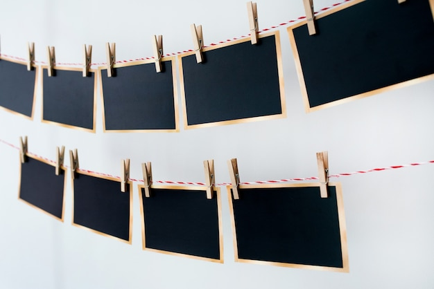 Old photographs hanging on rope on white background