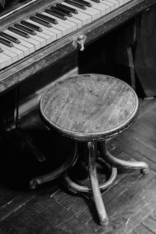 Old piano and chair. black and white . noise.