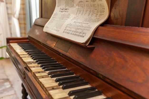 오래된 피아노. 사용하지 않는 오래된 피아노와 악보의 손상된 키를 닫습니다.