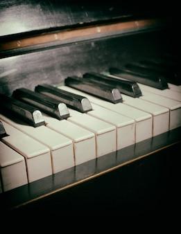 오래 된 피아노 키보드는 음악 배경으로 닫습니다. 먼지와 긁힌 자국이 있는 종이 질감
