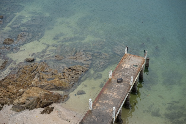 The old pier is beside the quiet sea. it is dangerous place to entry.