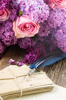 꽃과 푸른 깃털 펜으로 우표의 오래 된 더미
