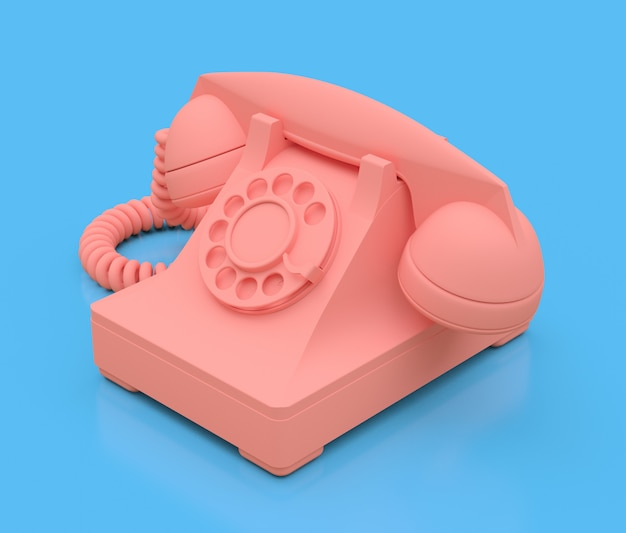 Old pink dial telephone on a blue surface