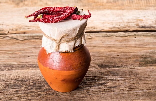 古い投手と木製のテーブルの赤唐辛子