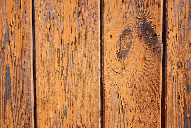 Old plank background with peeling, cracked paint, painted in terracotta color