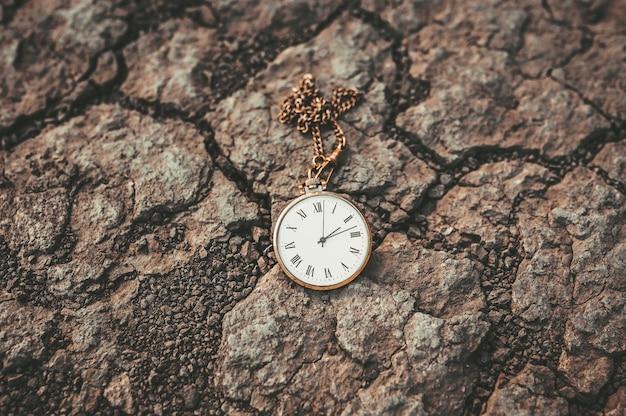 마른 땅에 오래 된 회중 시계. 시대와 시대의 변화.