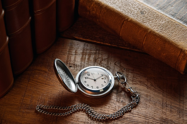 An old pocket watch with a chain lies on the table near vintage books.