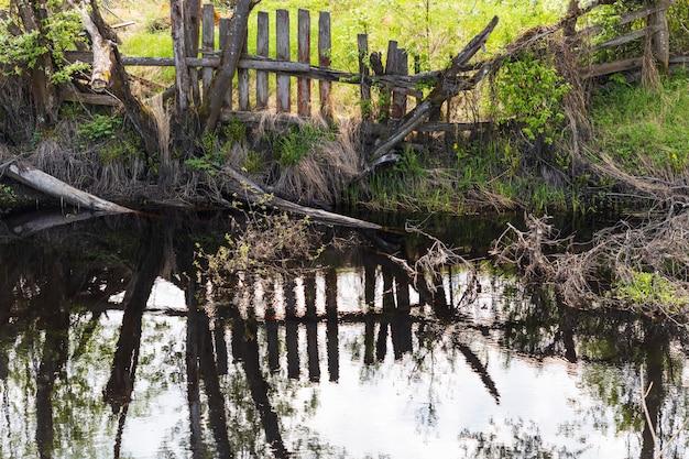 부러진 나무 울타리가 있는 마을의 오래된 연못.