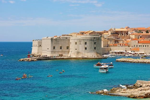 Старый порт дубровник со средневековыми укреплениями на адриатическом море, хорватия, европа
