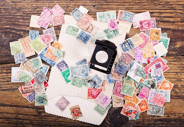 Old postage stamps from various countries and magnifying glass on wooden table