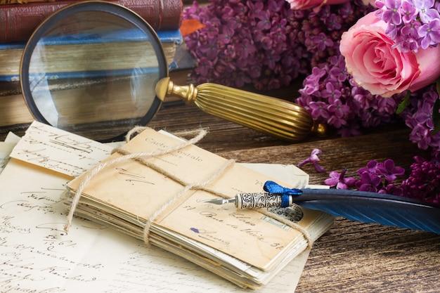 신선한 꽃과 푸른 깃털 펜으로 오래 된 우표