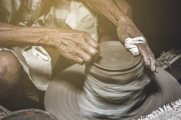 Old potter making bowl in pottery work background.