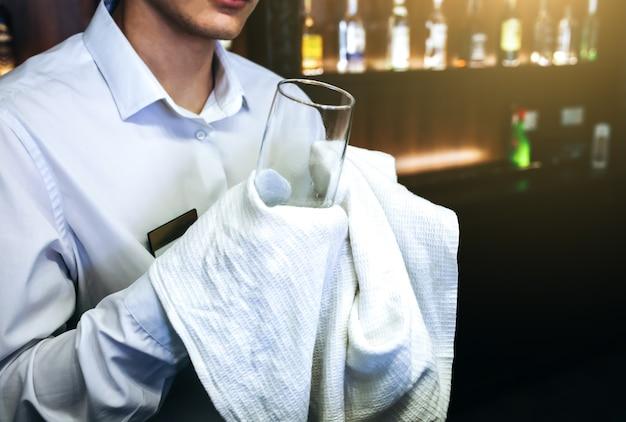 바텐더가 배경에 하얀 수건으로 유리를 청소하는 오래된 술집. 셔츠 유니폼에 빈 이름표 배지. 그의 직장에서 바텐더입니다.