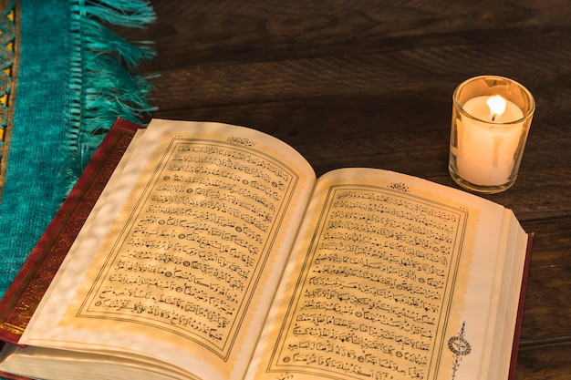 Old quran lying near candle