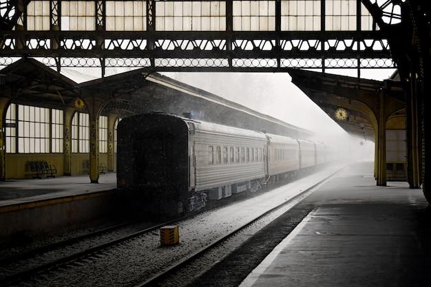 ロシアのサンクトペテルブルクの電車と空のプラットフォームの古い鉄道駅の屋内ビュー。雪の降る冬の日