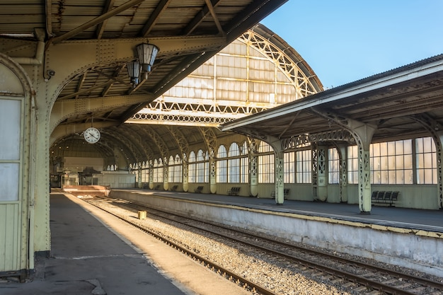 Old railway station with a platform clock empty without people.