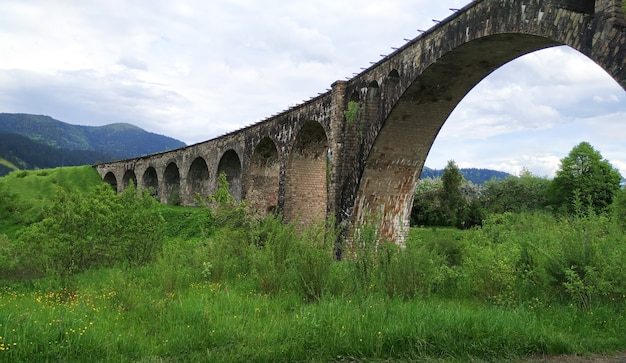 Old railway stone bridge or viaduct in spring mountains