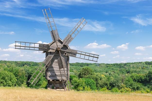 青い雲の空の前にある古い珍しい古代の木造風車