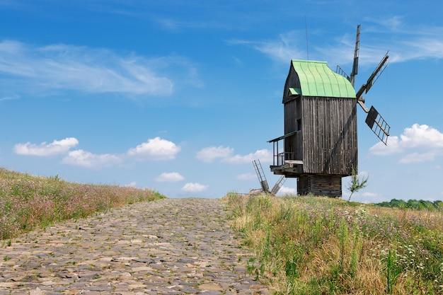 青い雲の空の前に石のブロック道路がある古い珍しい古代の木造風車