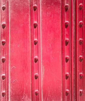 古い赤い板と金属のリベット