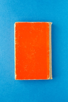 Old red book on a bright blue background.
