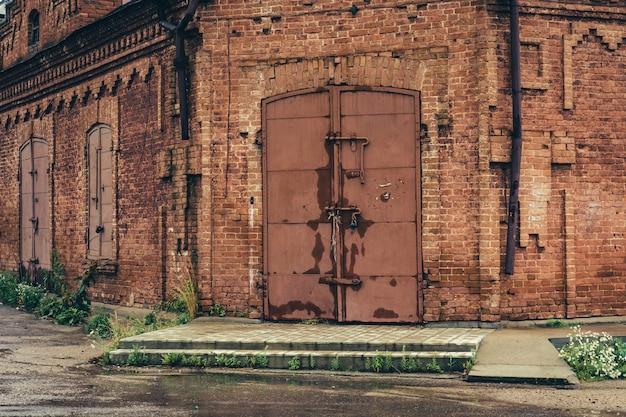 비오는 날씨에 거 대 한 철 잠겨 게이트 오래 된 붉은 벽돌 건물. 푸른 잔디는 건물 주변의 오래된 젖은 아스팔트를 통해 자랍니다.
