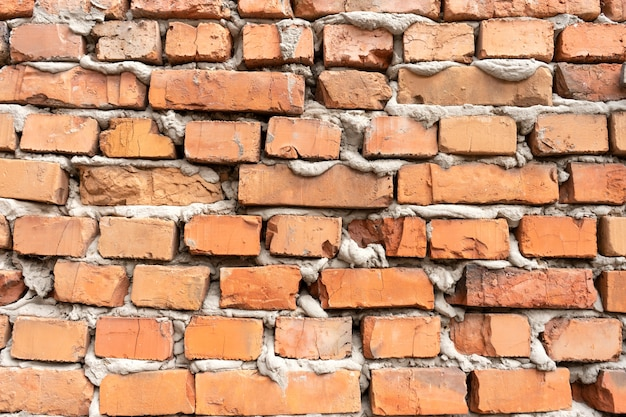 Old red brick falling apart wall texture background