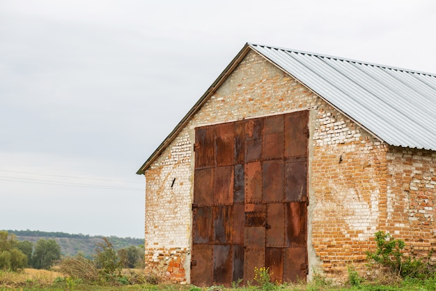Old red brick hangar with huge gates made of rusted metal. warehouse for rural products