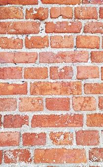 古い赤レンガの壁のテクスチャ。風化した石垣の背景の垂直写真