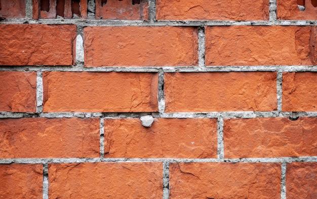 Старая красная кирпичная стена. кирпичи кладут рядами. каменная текстура гранж. фото высокого качества