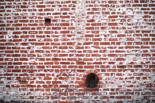 ひび割れとペンキの痕跡のある古い赤レンガの壁