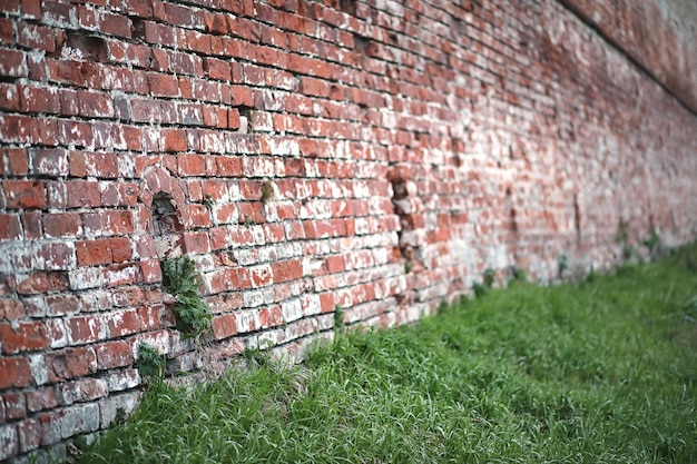 Old red brick wall with a crack and traces of paint