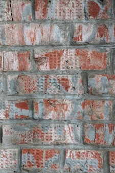 Old red brick wall with paint and cracks textured background