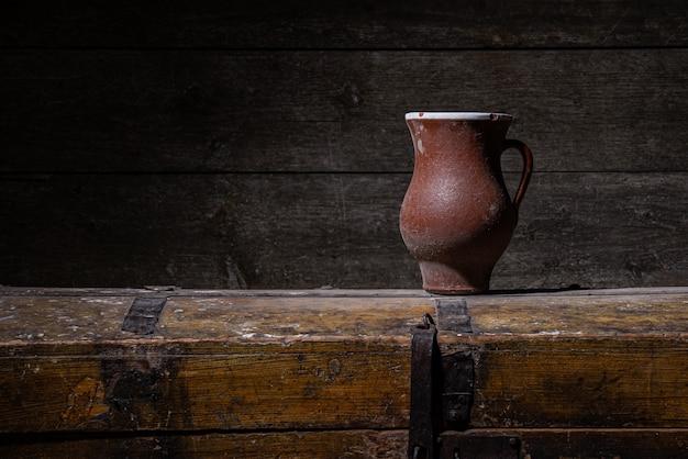 Старая керамическая глиняная посуда из красной глины на деревянном столе