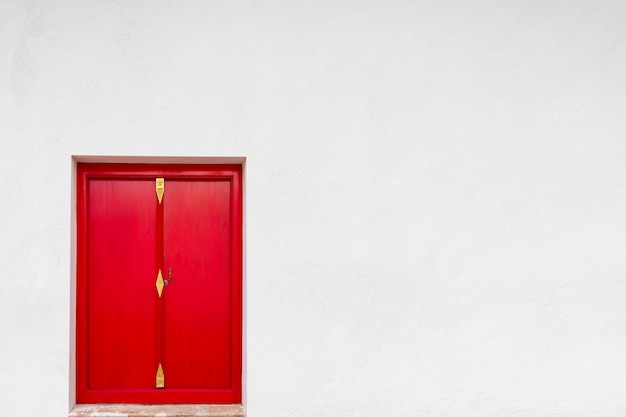 Old red door with white wall background.