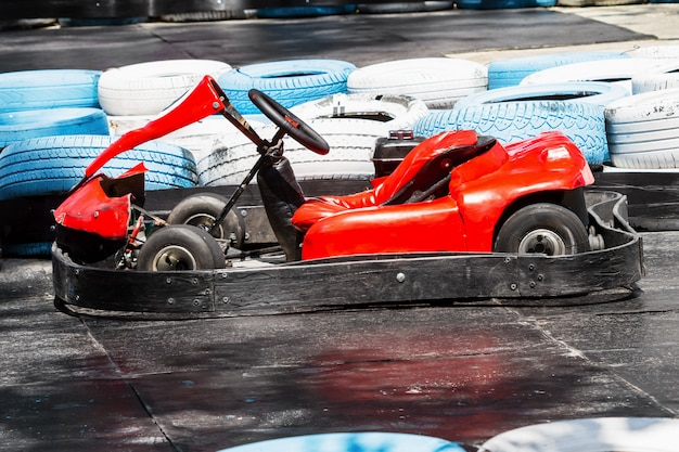 Old red kart against the tires on the kart track