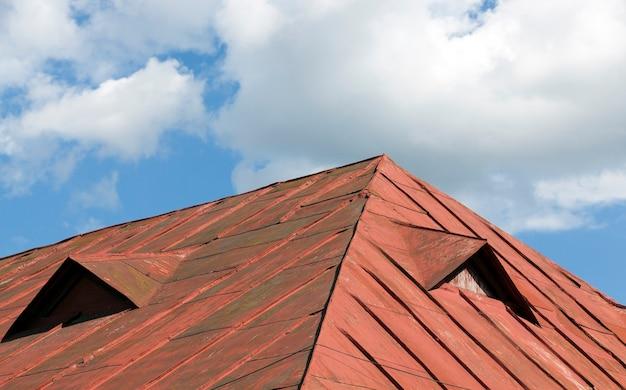 Старая красная металлическая крыша здания против голубого неба, много повреждений на металле, крупным планом