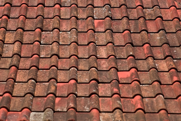Old red and orange weathered roof tiles texture background