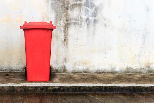 Old red plastic bin with brick wall background