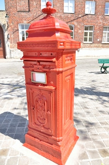 Old red post box in a street of bruges (belgium)